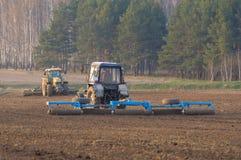 El tractor cultiva la primavera de caja Imagenes de archivo