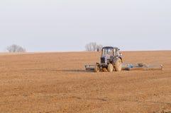 El tractor cultiva la primavera de caja Imágenes de archivo libres de regalías