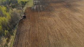 El tractor cultiva la tierra, arando el campo almacen de metraje de vídeo