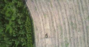 El tractor de la visión aérea conduce en campo cosechado a lo largo del bosque almacen de metraje de vídeo