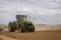 El tractor enorme quita el campo de los restos de la vegetación Primavera Región de Ucrania, Sumy Imagen de archivo