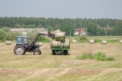 El tractor enviará la cosecha en el carro Imagen de archivo libre de regalías