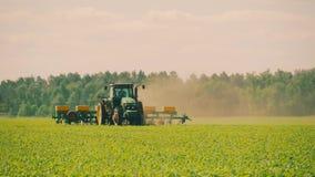 El tractor está protegiendo trigo con el herbicida que rocía, herbicidas de rociadura de la protección de las plantas almacen de metraje de vídeo
