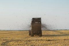 El tractor fertiliza el campo con el abono Un remolque grande sowing Agroindustria Poste antes de sembrar Contra el cielo Foto de archivo