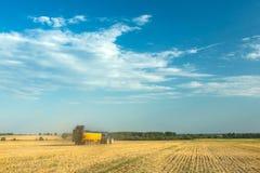 El tractor fertiliza el campo con el abono Un remolque grande sowing Agroindustria Poste antes de sembrar Contra el cielo Imagen de archivo