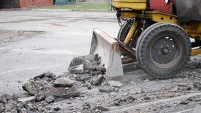 El tractor mueve el asfalto metrajes