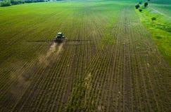 El tractor que rocía el campo con las sustancias químicas en la primavera Fotos de archivo libres de regalías