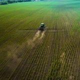 El tractor que rocía el campo con las sustancias químicas en la primavera Fotografía de archivo