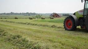 El tractor recoge el campo del heno Imagen de archivo
