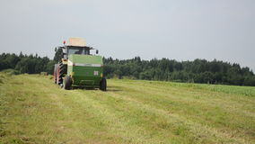 El tractor recoge el campo del heno Imágenes de archivo libres de regalías