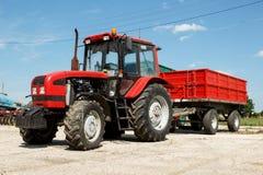 El tractor rojo con el remolque parqueó en un corral Fotografía de archivo libre de regalías