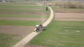 El tractor se mueve con el coche en el camino del campo Vuelo sobre un campo verde de la primavera con el grano de levantamiento  almacen de video
