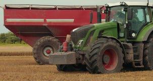 El tractor verde monta cerca del tractor amarillo con un remolque rojo Cosechadora que trabaja en el campo Campo de la cebada de  almacen de video