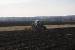El tractor viejo ara encima de la tierra Foto de archivo libre de regalías