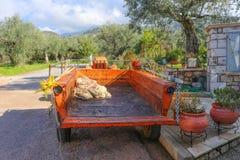 El tractor y el remolque con el rastrillo y el pruner verdes olivas parquearon en el pueblo griego con los olivares en la ladera  Imágenes de archivo libres de regalías