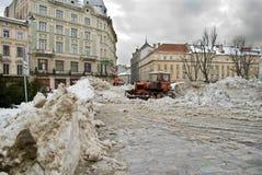 El tractor y trabajo para despejar nieve en el centro de ciudad Lviv Foto de archivo