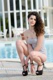 El traje de baño y los tacones altos que llevan de la mujer se sienta en sus piernas Fotos de archivo libres de regalías