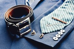 El traje de los hombres clásicos de la moda con la correa de cuero negra, el lazo azul rayado, los ufflinks de oro y el clip de l imagen de archivo libre de regalías