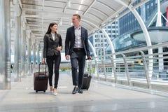 el traje del negro del desgaste del hombre de negocios y de la mujer de negocios camina así como el equipaje en la calle pública Foto de archivo libre de regalías