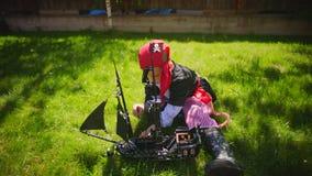 El traje del pirata del niño pequeño que lleva está jugando en la nave del juguete de piratas del Caribe en el césped en Hallowee almacen de video