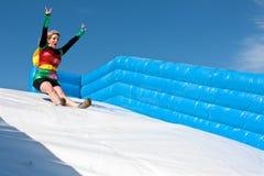 El traje del super héroe de la mujer que lleva va abajo de diapositiva de la raza de obstáculo Foto de archivo libre de regalías