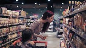 El traje femenino hermoso joven está eligiendo las especias en un supermercado local Su hijo del niño la espera pacientemente en  metrajes