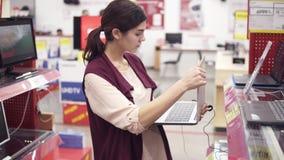 El traje femenino joven toma el ordenador portátil de la fila del escaparate y lo abre para examinar Elegir nueva electrónica cas almacen de metraje de vídeo