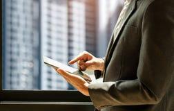 El traje que lleva del hombre de negocios está utilizando la tableta, hombre hace una pausa el windo Fotografía de archivo