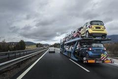 El transportador auto cargado por los pequeños coches está en la carretera fotos de archivo