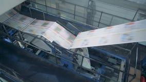 El transportador de la oficina de la impresión trabaja con el periódico, maquinaria automatizada almacen de video