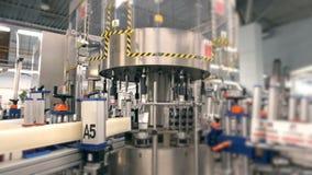 El transportador embotellador y de aislamiento alinea en la fábrica del lagar, máquina de etiquetado almacen de metraje de vídeo