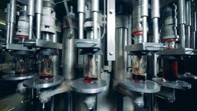 El transportador giratorio está vertiendo el alcohol en las botellas de cristal metrajes