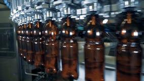 El transportador redondo está moviendo las botellas marrones con la cerveza almacen de metraje de vídeo
