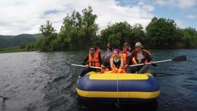 El transportar en balsa del verano: grupo de turistas y de viajeros que flotan en el río tranquilo en balsa