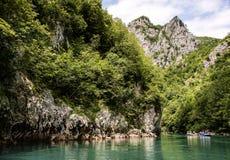 El transportar en balsa en el río de grupos de turistas a lo largo de las altas montañas Fotografía de archivo