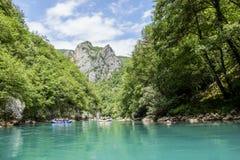 El transportar en balsa en el río de grupos de turistas y de altas montañas Foto de archivo libre de regalías