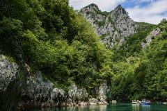El transportar en balsa en el río Tara de grupos de turistas a lo largo de las altas montañas Imágenes de archivo libres de regalías