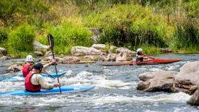 El transportar en balsa y el kayaking Un adolescente enganchó hábilmente a transportar en balsa bajo el control de padre-instruct Foto de archivo libre de regalías