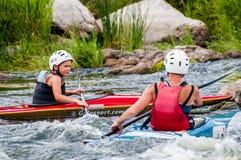 El transportar en balsa y el kayaking Un adolescente enganchó hábilmente a transportar en balsa bajo el control de padre-instruct Imágenes de archivo libres de regalías