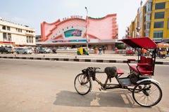El transporte indio tradicional del trishaw se coloca más allá del cine famoso de Raj Mandir fotografía de archivo libre de regalías