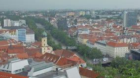 El transporte se está moviendo sobre los puentes a través del río de la MUR en la ciudad austríaca Graz en tiempo nublado almacen de metraje de vídeo