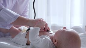 El tratamiento de los niños, doctor con el estetoscopio escucha los golpes de corazón del bebé en hospital almacen de metraje de vídeo