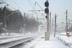 El tren acomete en invierno en la nube del polvo de la nieve Fotografía de archivo