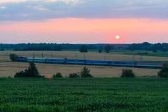 El tren, con los carros en las vías del tren en la puesta del sol en el campo Fotos de archivo