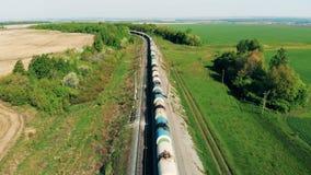 El tren de carga con los carros del tanque va en los campos cercanos ferroviarios largos 4K almacen de metraje de vídeo