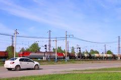 El tren de carga en ferrocarril y el coche se mueve en el camino cerca de hierba verde Fotos de archivo libres de regalías