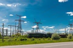 El tren de carga está pasando por las centrales y las líneas eléctricas térmicas Subestación eléctrica de la distribución imágenes de archivo libres de regalías