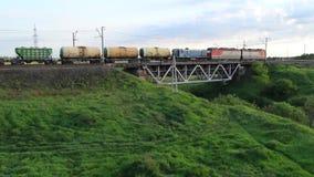 El tren de carga que viaja en el ferrocarril, tren pesado se mueve en el puente ferroviario metrajes