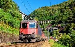 El tren de carga va abajo del paso de Gotthard - Suiza Imágenes de archivo libres de regalías