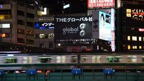 El tren de pasajeros pasa el horizonte de Shinjuku en la noche - Tokio Japón metrajes